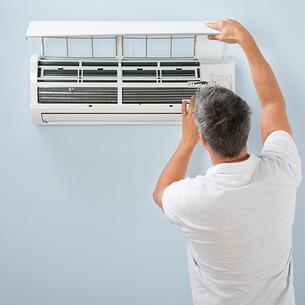 Man setting up a Ductless Mini-Split Air Conditioning Unit